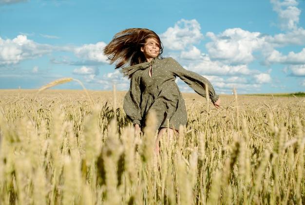 農家の手で小麦の芽。小麦の作物をチェックするフィールドを歩く農家