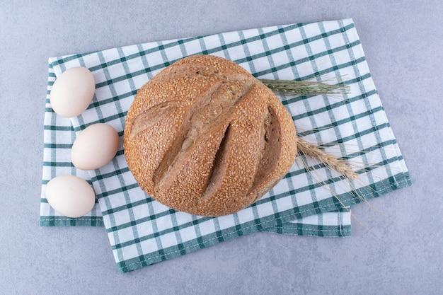 小麦の茎の卵と大理石の表面の折りたたまれたタオルの上に置かれたパンの塊