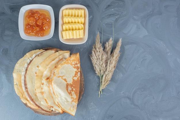大理石のテーブルの上に、小麦の茎、パンケーキ、ホワイトチェリージャムとバター。
