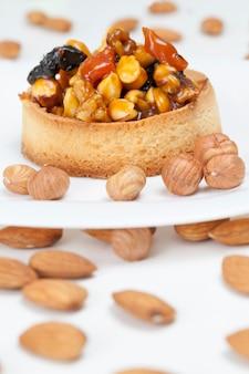 달콤한 속을 채운 밀 타틀렛, 헤이즐넛, 땅콩 및 기타 재료를 넣은 바삭한 타틀렛, 견과류와 말린 과일을 크림 카라멜에 넣은 밀 반죽 타틀렛