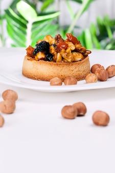 Пшеничная тарталетка со сладкой начинкой, хрустящая тарталетка с фундуком, арахисом и другими ингредиентами, тарталетка из пшеничного теста с орехами и сухофруктами в кремовой карамели