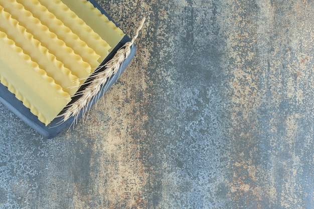 Grano con sfoglie di lasagne sul tagliere, sul piano di marmo.