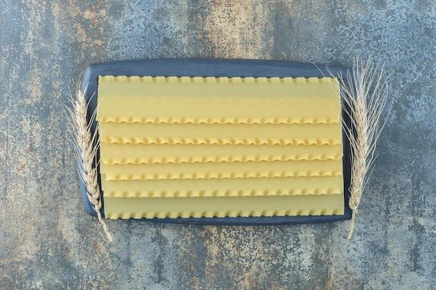 Пшеница с листами лазаньи на доске, на мраморной поверхности.