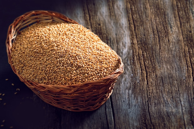 Wheat in wooden bowl on wooden background