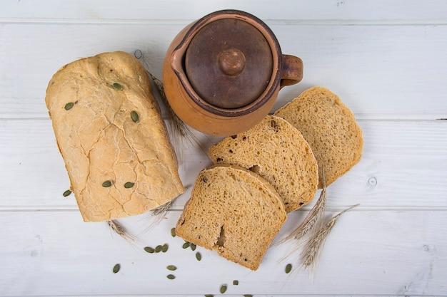 Пшеничные дрожжи деревенский хлеб с тыквенными семечками на фоне белой деревянной доски studio photo