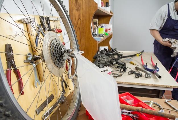 損傷した自転車の修復プロセスにおけるワークショップテーブル上のホイールと自転車の部品