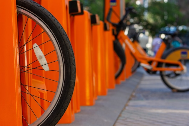 Wheel of bike on city orange parking station eco friendly transportation in urban area