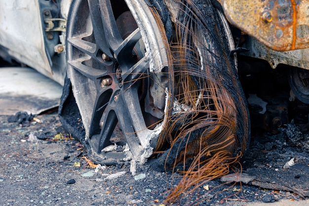 Wheel of burned car burnt flat tire on the car is on the gray asphalt road to illustrate