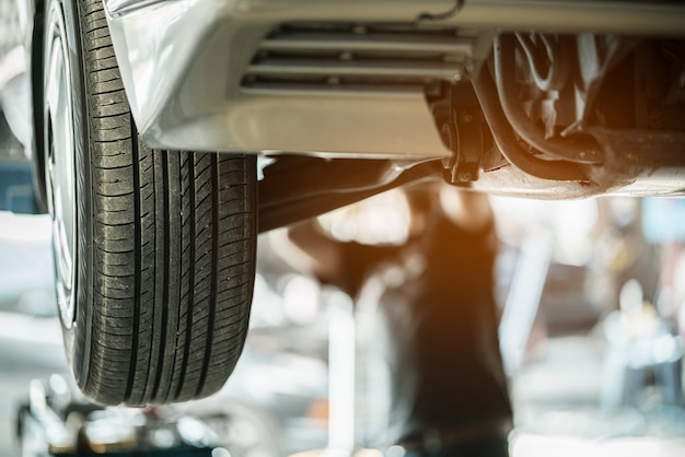 Wheel of car in automobile service with mechanic checking it at in the garage