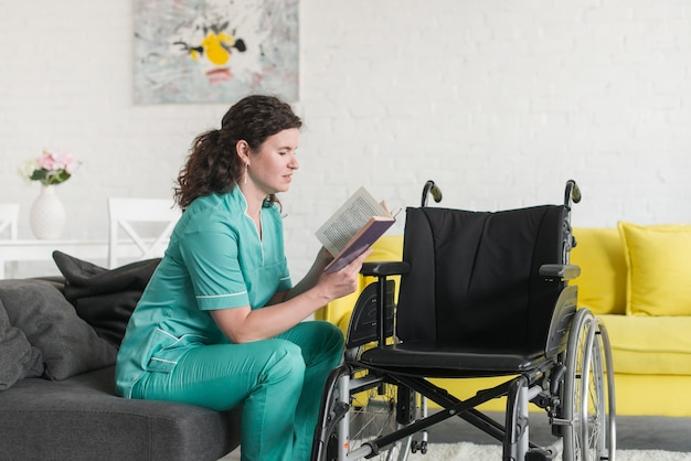 Wheel chair in front of nurse sitting on sofa reading book
