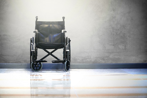 Wheel chair in hospital on raw cement background with light.