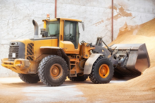 Wheel loader, excavator loading sand at construction site.