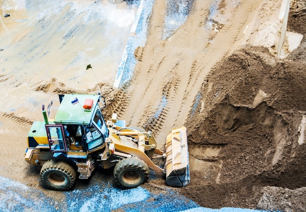 Wheel loader excavator unloading sand and stone works at construction site