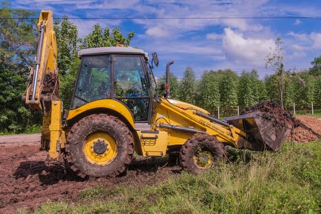 建設現場でのバックホウ積載土壌を備えたホイールローダーショベル。