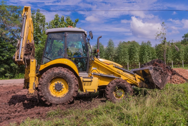 Wheel loader excavator with backhoe loading soil at construction site.