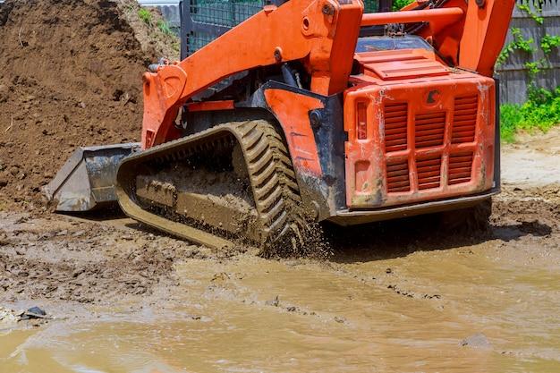Wheel loader excavator with backhoe unloading earth at eathmoving works construction site quarry