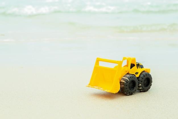 砂の上のホイールローダーのおもちゃ、ビーチに近いコンストラクターのおもちゃの乗り物