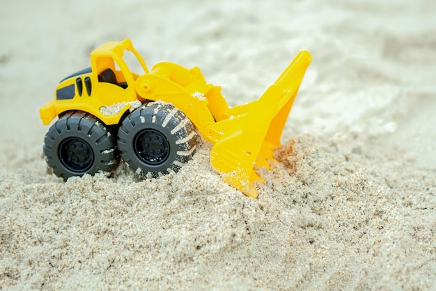 砂の上のホイールローダーのおもちゃ、コンストラクターのおもちゃの乗り物