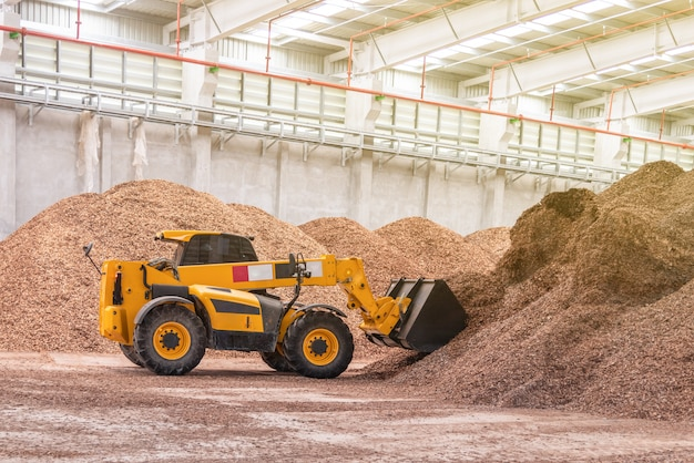 Wheel loader truck working at factory wood chipper