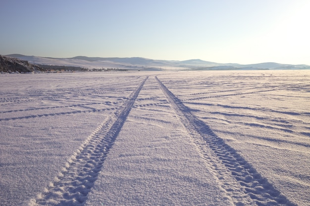 Wheel tracks on the winter road covered with snow