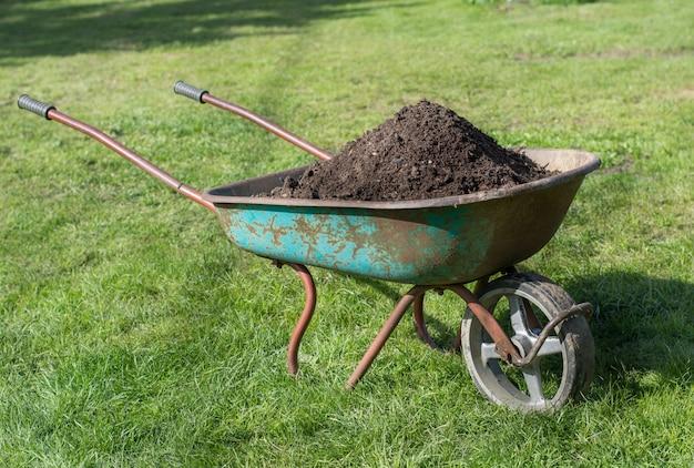 芝生の上の堆肥でいっぱいの手押し車