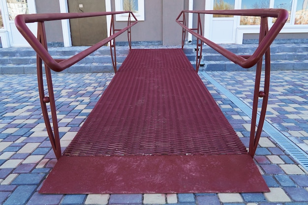 Wheelchair access ramp for entrance of residential multistory building, city street and tiles sidewalk