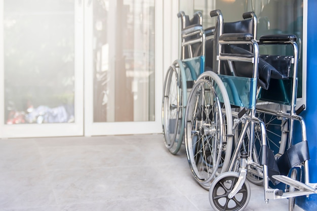 Wheelchair are fold and park in the hospital entrance, medical equipment for use as a means of transport by a person who is unable to walk as a result of illness, injury, or disability, copy space