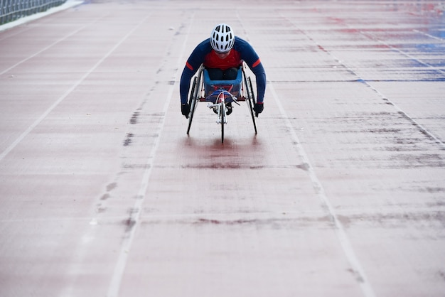 Wheelchair athletics. paralympic champion in sport wheelchair approaching finish line while having racing competition at outdoor track and field stadium
