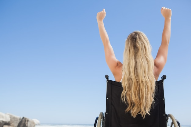 Wheelchair bound blonde sitting on the beach with arms up