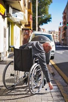 Инвалид-колясочник поднимает прозрачную пластиковую бутылку, брошенную и брошенную на пол, чтобы бросить ее в контейнер для утилизации мусора и избежать загрязнения. избегайте пластмасс