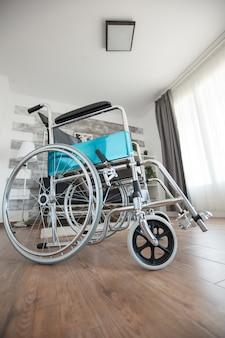 歩行障害のある患者のための、誰もいない部屋の車椅子。民間のナーシングホームの部屋には患者がいません。セラピーモビリティは、高齢者や障害者の歩行障害をサポートします