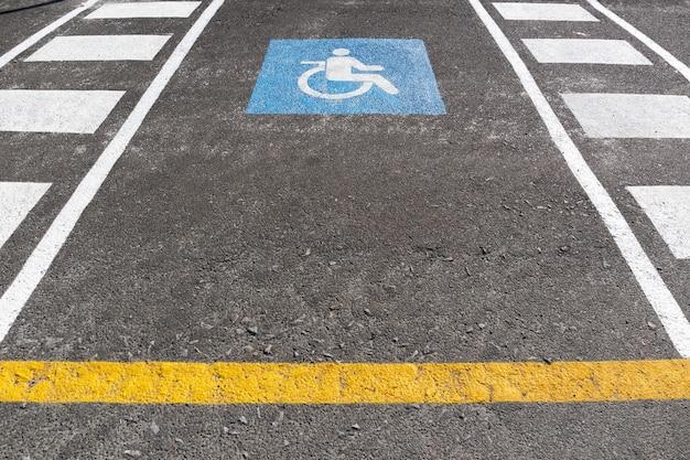 야외에 휠체어 주차 공간입니다. 아스팔트에 그려진 교통 표지 장애인 기호