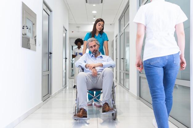 병원 복도에서 전문 여성 의사와 간호사 전문 직원이있는 휠체어 환자