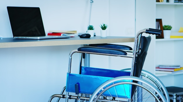 Wheelchair for people with mobility disability in empty room.