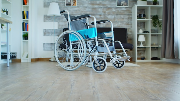 Wheelchair for people with walking handicap in empty room.