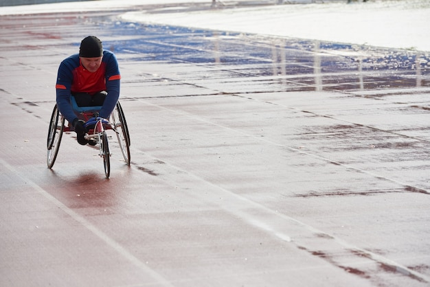Wheelchair racing. strong-willed handicapped male athlete in sport wheelchair training at outdoor track and field stadium on cold rainy day