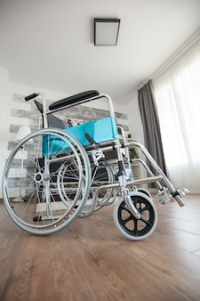 Wheelchair in a room with nobody in it for patients with walking disability. no patient in the room in the private nursing home. therapy mobility support elderly and disabled walking disability impair