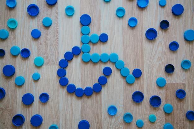 Знак инвалидной коляски из пластиковых крышек фон синих пластиковых крышек от бутылок концепция переработки