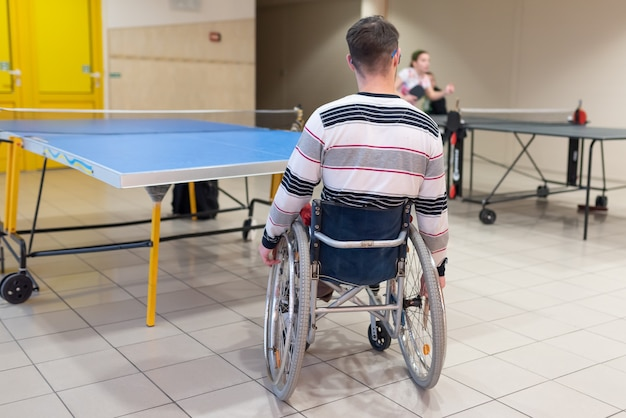 Wheelchair user playing table tennis. from the back. for any purpose.