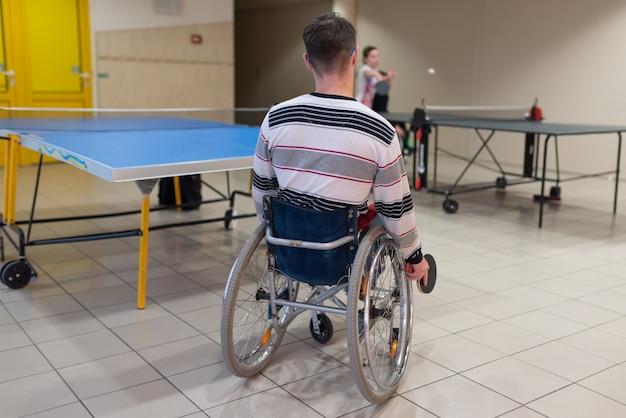 탁구를 치는 휠체어 사용자. 뒤쪽에서. 어떤 목적을 위해.