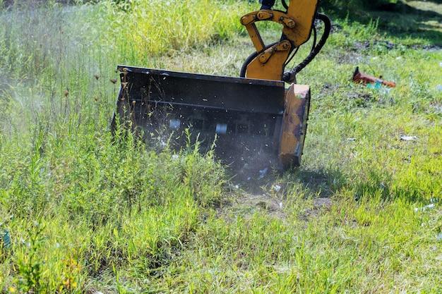 郊外の高速道路の道端を運転する外部の取り外し可能な取り付けられた芝刈り機装置を備えた車輪付きトラクター芝刈り機
