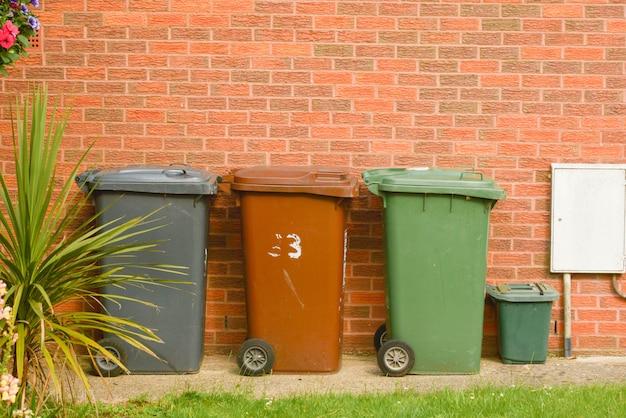 Wheelie bin in front of a house, brick wall