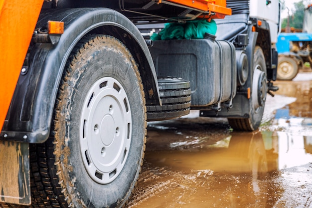 Wheels of a big truck in a mud puddle.