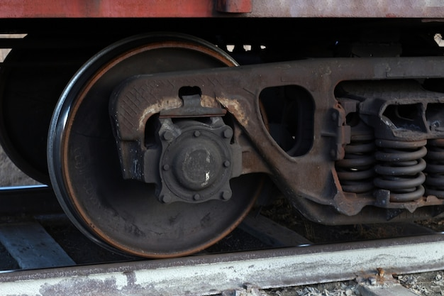 The wheels of an old rusty broken freight train are on the tracks
