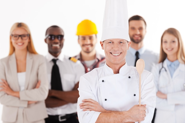 나는 커서 요리사가 될 것이다. 제복을 입은 자신감 있는 남성 요리사가 팔짱을 끼고 웃고 있는 동안 다양한 직업을 가진 사람들이 뒤에 서 있습니다
