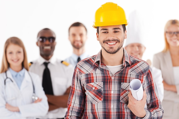 나는 커서 엔지니어가 될 것이다. 다른 직업을 가진 사람들이 배경에 서 있는 동안 청사진을 들고 웃고 있는 안전모를 쓴 자신감 있는 청년