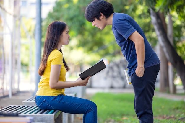 Сидя на скамейке в парке, симпатичная улыбающаяся молодая азиатская женщина смотрит на книгу своего парня, читая книгу.