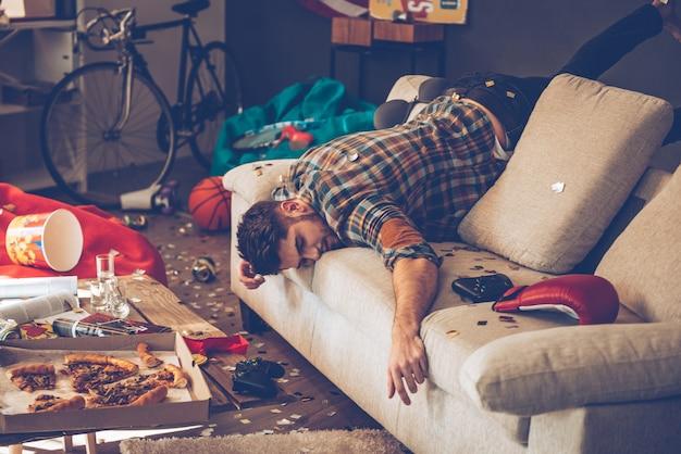 Когда вечеринка окончена. молодой красавец потерял сознание на диване в грязной комнате после вечеринки
