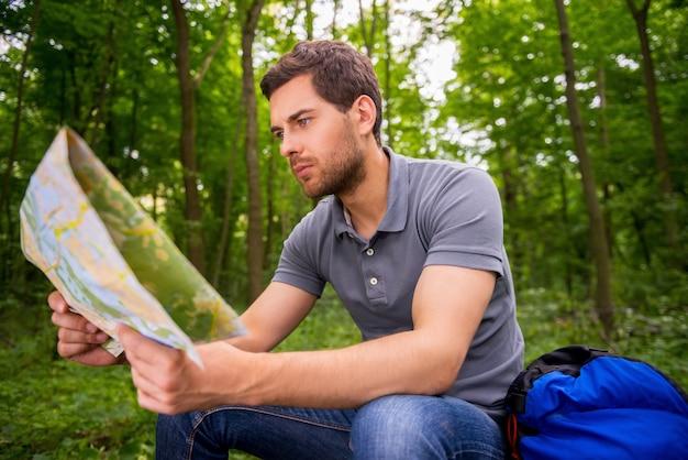 Где я? сосредоточенный молодой человек с изучением карты, сидя в лесу с рюкзаком, лежащим рядом с ним