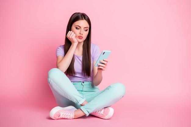 Где мой любит комментарии. скучающая разочарованная девушка сидит на полу, скрестив ноги, использует сообщение типа смартфона, подождите, пока подписчики носят бирюзовые фиолетовые брюки, изолированные на пастельном цветном фоне